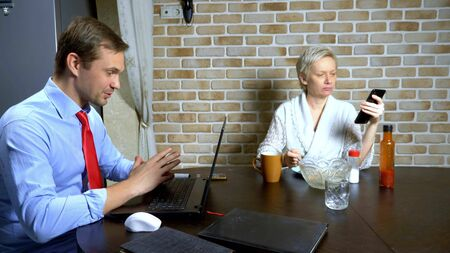 a man working at home on the laptop in the kitchen, wife eats
