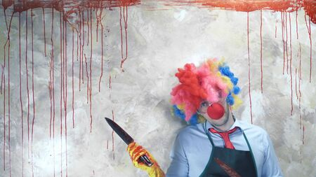 the man in the clown suit in the background of the bloody wall with a knife Zdjęcie Seryjne - 150413094