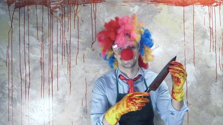 the man in the clown suit in the background of the bloody wall with a knife