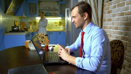 a man holds a video conference at home in the kitchen his wife eats at the table