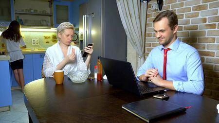 a man working at home on the laptop in the kitchen, wife eats Zdjęcie Seryjne - 149068166