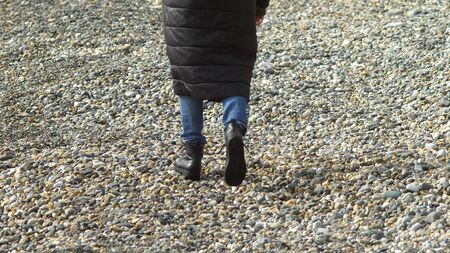 woman in coat walking on the pebble beach. copy space Zdjęcie Seryjne - 149068179