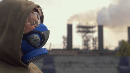 A woman in a respirator stands on the background of smoking factory pipes