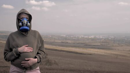 a pregnant woman in a respirator outdoors. environmental issues, pandemic Zdjęcie Seryjne - 149068128