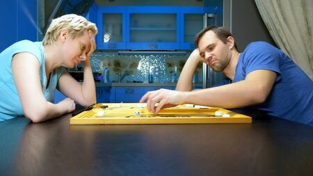man and woman playing backgammon in the kitchen. family leisure