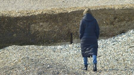 woman in coat walking on the pebble beach. copy space