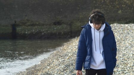a guy with headphones and jacket walks in pebble beach alone