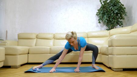 woman goes in for sports at home, in the living room. Zdjęcie Seryjne - 146945024