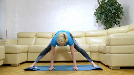 woman goes in for sports at home, in the living room.