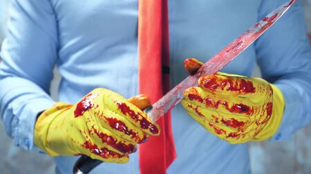 closeup. male hands in rubber gloves holding a bloody knife