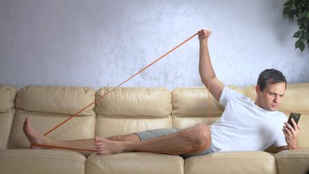 man on the couch does sports with an elastic band and uses a smartphone Zdjęcie Seryjne