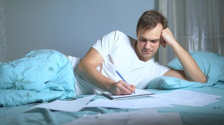 A man writes on paper documents lying in bed. work at home.