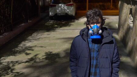 closeup. portrait of a teenager boy in a respirator in open space.