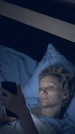 vertically. woman suffering from insomnia uses a smartphone while lying in bed Zdjęcie Seryjne - 146435191