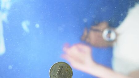 blurred background. a man throws a coin into the water. under the water