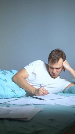 vertical shot. A man writes on paper documents lying in bed. work at home.