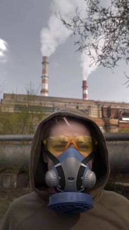 vertically. A woman in a respirator. the background of smoking factory pipes Zdjęcie Seryjne