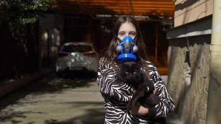 girl in a respirator on the street holds a black cat. copy space