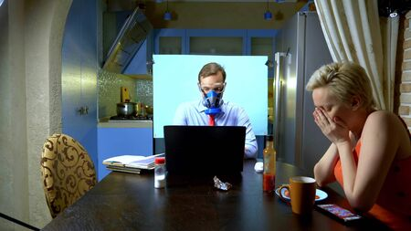 A man in a respirator holds a video conference at home in the kitchen.