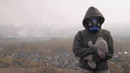 girl in respirator with a soft toy on the background of Smoking factory chimneys