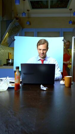 vertically. A man holds a video conference at home in the kitchen, his wife looks in the refrigerator Zdjęcie Seryjne - 146435378