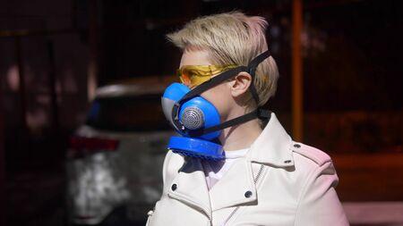 a woman with short hair a respirator outdoors. closeup Zdjęcie Seryjne - 146435466