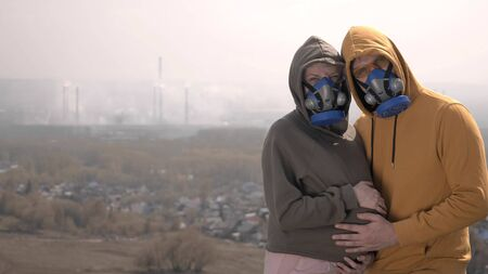 pregnant woman and her man in respirators on the street against factory pipes