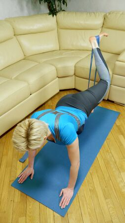 vertical shot, woman has home sport using stretch tape.
