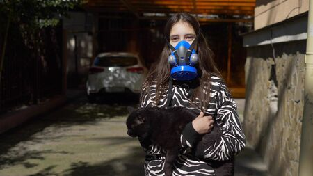 girl in a respirator on the street holds a black cat. copy space Zdjęcie Seryjne - 146435473