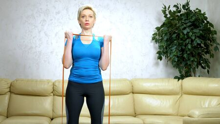 woman has home sport using stretch tape. strength training, aerobic exercise