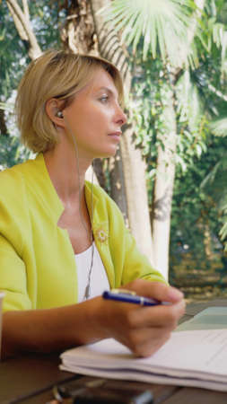 vertically. beautiful business woman in yellow jacket holding video conference via laptop in an outdoor cafe Zdjęcie Seryjne - 159264180