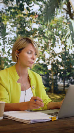 vertically. beautiful business woman in yellow jacket holding video conference via laptop in an outdoor cafe Zdjęcie Seryjne - 159264231