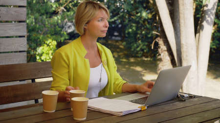 workaholic woman working on laptop in cafe outdoors with three cups of coffee. Zdjęcie Seryjne - 159264318