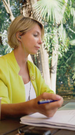 vertically. beautiful business woman in yellow jacket holding video conference via laptop in an outdoor cafe Zdjęcie Seryjne - 159264244