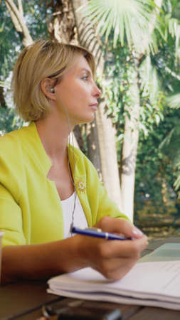 vertically. beautiful business woman in yellow jacket holding video conference via laptop in an outdoor cafe