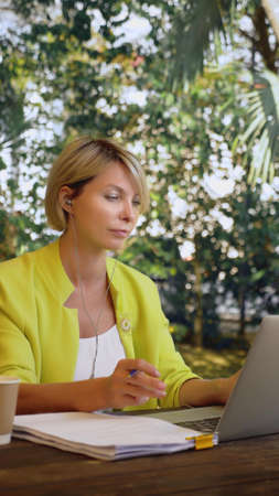 vertically. beautiful business woman in yellow jacket holding video conference via laptop in an outdoor cafe Zdjęcie Seryjne - 159264323