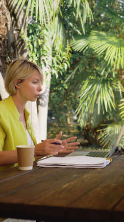 vertically. beautiful business woman in yellow jacket holding video conference via laptop in an outdoor cafe Zdjęcie Seryjne - 159391881