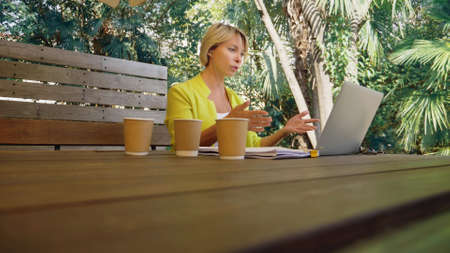 workaholic woman working on laptop in cafe outdoors with three cups of coffee. Zdjęcie Seryjne - 159264263