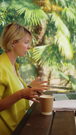 vertically. beautiful business woman in yellow jacket holding video conference via laptop in an outdoor cafe Zdjęcie Seryjne - 159391885
