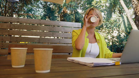 workaholic woman working on laptop in cafe outdoors with three cups of coffee.