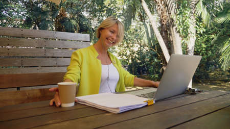 close-up. portrait of a beautiful business woman in a yellow jacket holding a video conference in a summer cafe Zdjęcie Seryjne