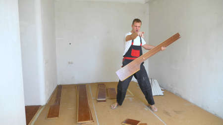 a man builder in overalls pretending to play the guitar on a laminate board