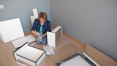 woman collects furniture while sitting on the floor at home, copy space Zdjęcie Seryjne