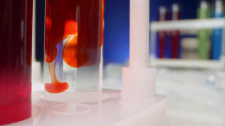 chemical experiments. red liquid dissolves in a clear liquid in a test tube
