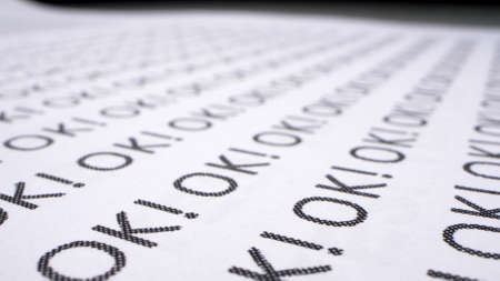 text background. the word ok written many times on a white piece of paper Фото со стока