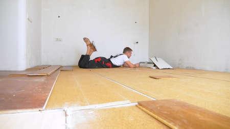 Builder in renovated room lying on floor using smartphone