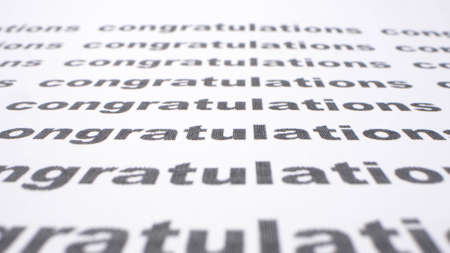text background. word congratulation printed on a sheet of paper with a list