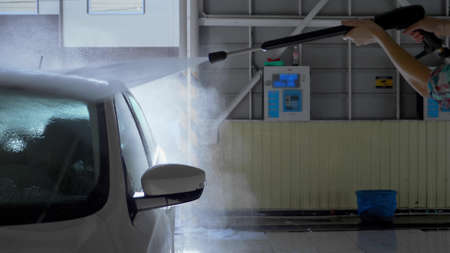 young woman washes a car at a self-service car wash. overall plan Zdjęcie Seryjne