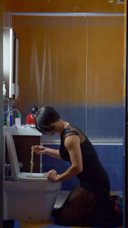 vertically. a man disguised as a woman eating noodles from the toilet
