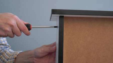 close-up. male hands screw the bolt to a piece of furniture with a screwdriver